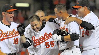 The Orioles' Ramon Hernandez (55) is surrounded by teammates after driving in the winning run against Pirates in the ninth inning last night in Baltimore.