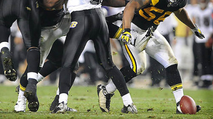 LaMarr Woodley picks up a fumble that he returns for a touchdown against the Ravens in the third quarter last night at Heinz Field.