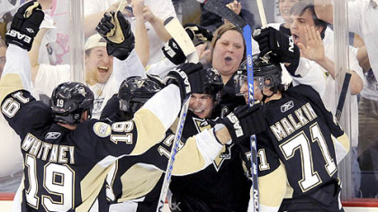 The Penguins celebrate the winning third-period goal.