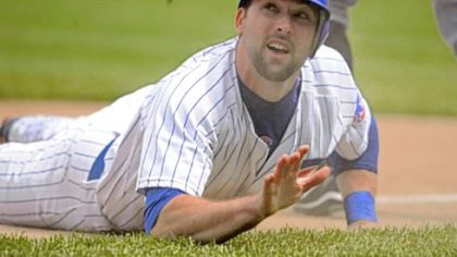 The Cubs' Mark DeRosa looks up at umpire Jim Wolf after sliding safely into third base against the Pirates in the third inning yesterday.