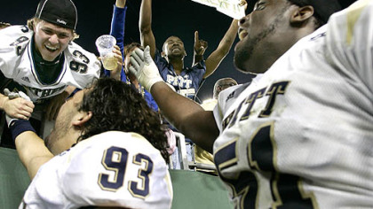 Pitt&#039;s Gus Mustakas (93) and Tommie Duhart (51) celebrate their 26-21 upset over South Florida  with fans in Tampa, Fla.