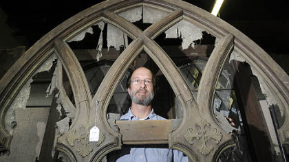 David Arnold, consignment manager at Dargate Auction Galleries, looks through a wooden lancet tracery panel that screened a church's pipe organ, once part of Vernon Regal's collection.