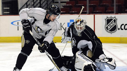 Sidney Crosby tries to wrap the puck around Dany Sabourin at practice yesterday at Mellon Arena.
