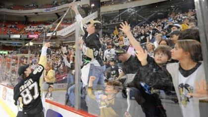 Sidney Crosby gives away his stick to a fan after the Penguins' 4-2 victory over Philadelphia at Mellon Arena last night. The equipment giveaway is a fan-appreciation tradition after the last home game of the season.