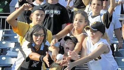 Fans bobble a ball thrown out by Pirates pitcher Ian Snell after their last game of the 2008 season.  The fans couldn''t hang onto the ball and it fell into the dugout.