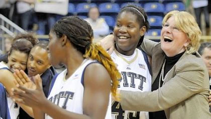 Pitt coach Agnus Berenato hugs Mercedes Walker after defeating West Virginia in overtime Feb. 26. Berenato signed a new contract yesterday to stay with the Panthers through the 2015-16 season.