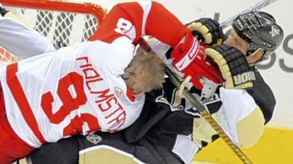 Gary Roberts, right, clears Detroit&#039;s Tomas Holmstrom from in front of the net in the first period last night.