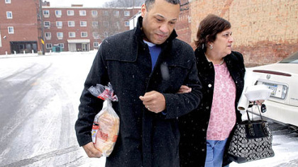 Ellwood City Police Chief Richard McDonald helps Doreen Welsh walk through an icy parking lot in downtown Ellwood City on Tuesday.