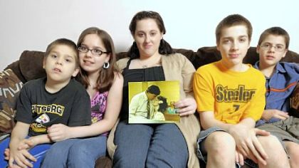 Children of Sandee McCann in Georgia: From left,  Chris Gebert, Bria Gebert, Alexandra Firestone (holding a photo of her mother and father), Dylan Gebert and Jude Gebert.