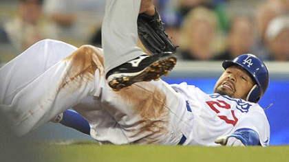 Dodgers right fielder Matt Kemp ducks under the tag of the Pirates' third baseman Jose Bautista between second and third base as he is caught in a rundown during the first inning of last night's baseball game, in Los Angeles. Kemp made it safely to third on the play.