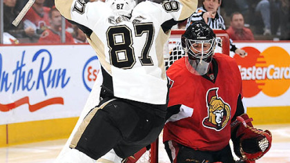 Sidney Crosby celebrates his third-period goal in front of Senators goalie Martin Gerber last night at Scotiabank Place in Ottawa.