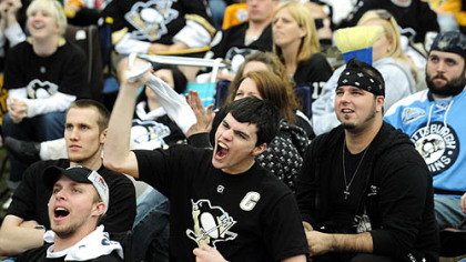 Penguins fan Kyle Stunkard, center, waves his towel as they watch the game via the jumbotron on the lawn at Mellon Arena.