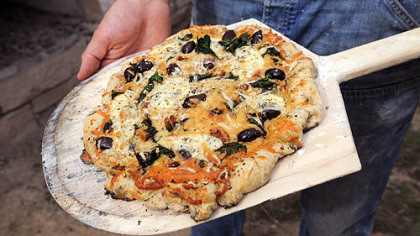 A Garlic, Spinach and olive pizza baked in Braddock&#039;s community bread oven.