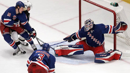 New York Rangers goalie Henrik Lundqvist, right, blocks a shot on the goal from the Penguins&#039; Sidney Crosby as he is defended by teammate  Marc Staal (18)  as Michal Rozsival (3), looks on during tonight&#039;s Game 4 of their second-round playoff series.