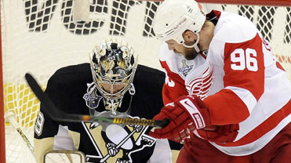 The Penguins' Marc-Andre Fleury makes a save on the Red Wings' Tomas Holmstrom in the first period.