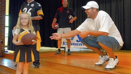 Wyland kindergartener Jessica Leventry receives an autographed football from Ben Roethlisberger. Jessica, won a raffle for the ball.