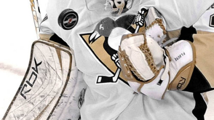 Penguins goalie Marc-Andre Fleury juggles the puck as he makes a third-period save against the New Jersey Devils last night. Fleury stopped all 31 Devils shots in the Penguins' 2-0 win.