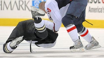 The Penguins' Paul Bissonnette is taken down by the Capitals' Matt Bradley in a second-period scuffle last night.