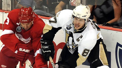 Sidney Crosby passes the puck around the Red Wings&#039; Nicklas Lidstrom in the second period Monday at Joe Louis Arena in Detroit.
