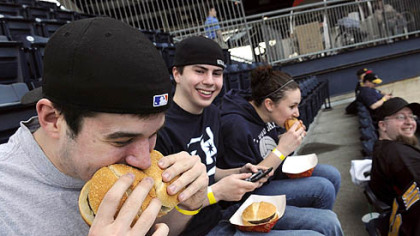Jim Lewis, 21, of Coraopolis playfully stuffs two hamburgers in his mouth while his friend, Brenden Klink, 20, of West End, looks on at the all-you-can-eat section at the PNC Park during yesterday's Pirates-Cubs game. At right is their friend, Brittany Yourkonis, 19.