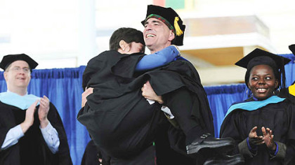 To a rousing ovation, Randy Pausch carries his wife, Jai back to their seats after giving the charge to the graduates at CMU's 111th commencement ceremony May 18.
