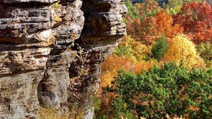 A towering sandstone cliff juts out into the fall colors of the gorge at Conkles Hollow in Hocking Hills State Park in Logan, Ohio.