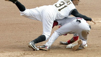 The Reds' Brandon Phillips rolls into Pirates shortstop Luis Rivas, who completes the throw to finish a double play on Jeff Keppinger in the eighth inning.
