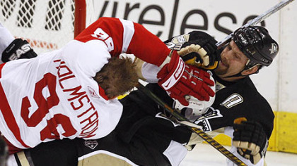 Detroit's Tomas Holmstrom, left, takes out Gary Roberts during first period action in Game 3 of the Stanley Cup Final at Mellon Arena.