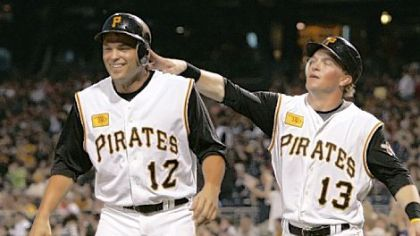 Pirates&#039; Nate McLouth, right, pats teammate Freddy Sanchez on the helmet after the two scored on a double by Ryan Doumit.