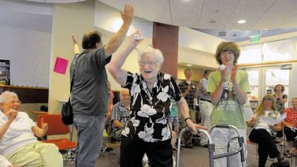 Virginia Kotow cheers as she scores a strike in a game of Wii bowling.