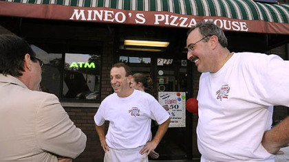 Mineo's Pizza House owners Jon, center, and Dominic Mineo, talk with city council president Doug Shields, left, during the 50th Anniversary event at the Squirrel Hill insitutution.