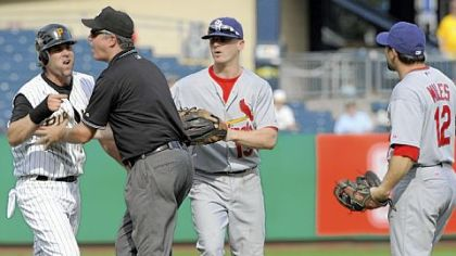 The Pirates' Doug Mientkiewicz is kept away from the Cardinals' Aaron Miles in the eighth inning.