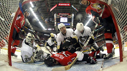 Ottawa's Nick Foligno absorbs the wrath of a host of Penguins in the Penguins' crease Monday in Game 3.
