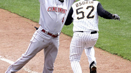 Cincinnati's Brandon Phillips can't get to the ball as Pirates pitcher Franquelis Osoria is safe at first on a bunt.