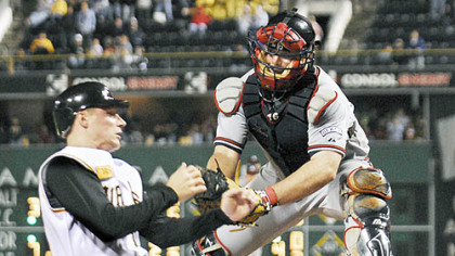 The Pirates' Brian Bixler slides into home plate to score the team's second run of last night's game as Atlanta Braves catcher Brian McCann misses the tag in the seventh inning at PNC Park.