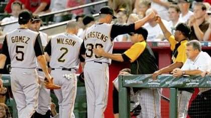 Jeff Karstens, center, is welcomed back to the dugout at the end of the bottom of the eighth inning == moments after he lost his no-hit and perfect-game bid at Chase Field.
