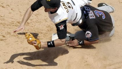 Pirates' Chris Gomez flies over Mets' Damion Easley after getting him out at second base.