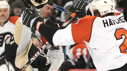 Penguins Petr Sykora takes a puck and stick from Flyers Derian Hatcher.