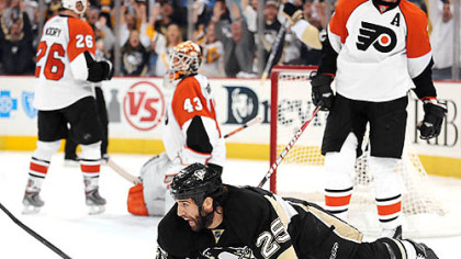 Penguins Max Talbot is knocked to the ice after scoring the winning goal.
