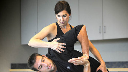 Steelers tight end Matt Spaeth is helped with a yoga pose by instructor Karen Conley during an optional yoga class available as part of their in-season regimen at the Steelers' South Side training facility. Ms. Conley, along with her husband, Sean Conley, below, a former NFL player, are co-owners of three yoga studios under the name of Amazing Yoga and began teaching yoga to the Steelers in spring 2007.