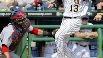 Pirates outfielder Nate McLouth scores as the ball flies over the head of Cardinals catcher Jason LaRue in the first inning  of yesterday's game at PNC Park.