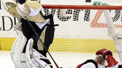Tomas Holmstrom ends up in the net as he's injured behind Penguins goalie Marc-Andre Fleury in the third period.