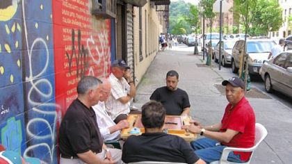 A group of men play dominoes on Ellwood Street in Washington Heights, New York City, a half block from Pedro Alvarez's apartment building.