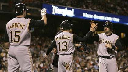 Andy LaRoche (15) and Nate McLouth (13) congratulate teammate Ryan Doumit after scoring against the San Francisco Giants during the seventh inning of yesterday's baseball gam in San Francisco.
