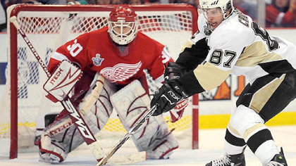 Sidney Crosby faces off agsint Red Wings goalie Chris Osgood last night at Joe Louis Arena in Detroit.