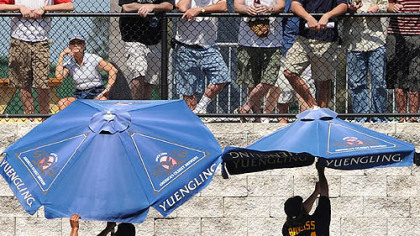 Players in the bullpen struggle with umbrellas as fans watch yesterday in Clearwater, Fla.