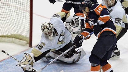 Penguins goalie Ty Conklin (35) blocks a shot on goal from New York Islanders' Richard Park (10) as teammate Sergei Gonchar (55), of Russia, helps defend during the third period of last night's  hockey game in Uniondale, N.Y.