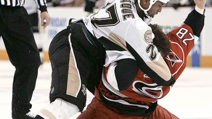 The Penguins' Georges Laraque and the Hurricanes' Wade Brookbank fight in the first period.