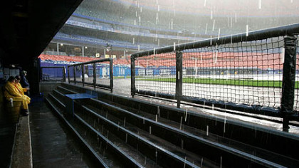 Heavy rain falls into the visitors dugout before the Pirates game against the Mets at Shea Stadium was postponed because of rain in New York.