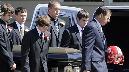 Pallbearers carry the casket of John Challis and his Freedom football helmet yesterday into SS. Peter and Paul Roman Catholic Church in Beaver for his funeral.